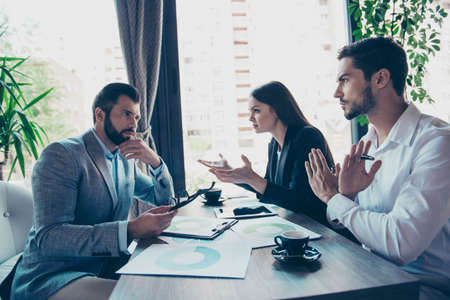 똑똑한 옷을 입은 3 명의 비즈니스 파트너가 레스토랑에서의 회의에서 회사의 재정에 관해 논의하고 있습니다. 모두 혼란스럽고 논쟁을하며 부인하고