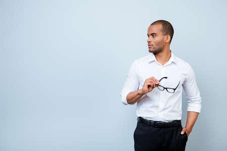 黒眼鏡、見て、copyspace を保持コピー スペースの近くの純粋な青色の背景の正式な衣装で深刻なムラート アメリカ ビジネスの男が立っています。