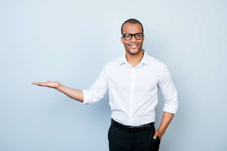 Young cheerful successful african lawyer on the pure light blue background is smiling, standing in formal wear and is holding the copyspace Stock fotó