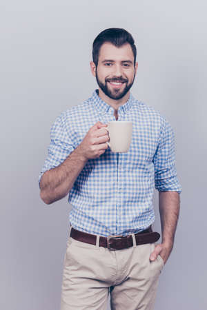 Young dreaming brunet bearded worker in formal wear is standing with the mug of tea isolated on pure background. He is relaxed, happy, smiling Stock Photo