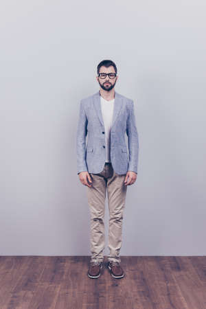 he: Full size portrait of stylish young bearded man standing near gray background and wooden floor. He looks stunning! in a suit and with glasses