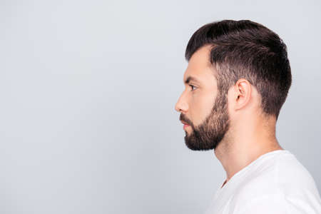 Side profile portrait of a brunet guy, isolated on pure light blue background.