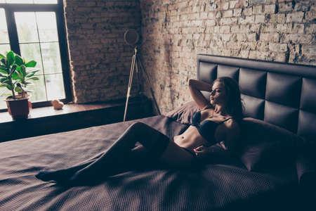 De overweldigende jonge sexy brunette ligt op het bed in donkere zolderruimte.