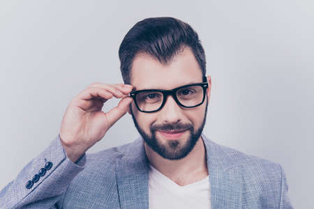 Successful young handsome brunet bearded businessman in formal outfit and black glasses on pure background. So cheerful and stylish, attractive and smart