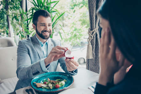 Cheerful romantic brunet bearded guy is proposing to his amazed brunette lover, they are in a fancy restaurant, in formal outfit, so happy! Stock Photo