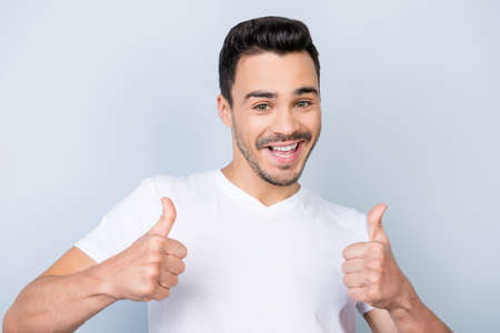 Smiling young stylish bearded brunet student in  casual white t shirt is standing on light background and show thumbs up with flirty smile and glance Stock Photo