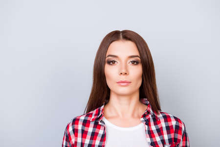 pedant: Close up portrait of serious young freelancer brunette lady, she stands in checkered shirt on pure light background, so severe and strict Stock Photo