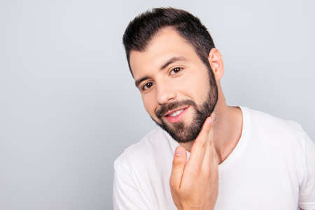 Close up portrait of a happy guy, who got his trendy fashionable cut of the beard.