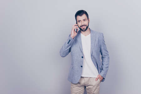 Cheerful brunet bearded businessman is smiling, talking to business partner about success of the company. Income increased, he is happy, wearing casual smart, standing on a pure light background