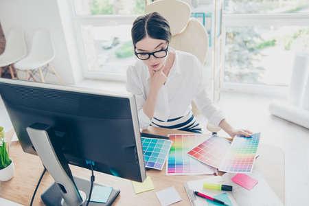 Hoogste mening van intelligente modieuze jonge Aziatische grafische ontwerper werkt met peinzende kleurensteekproeven. Ze is een succesvolle zelfstandige kunstenaar Stockfoto