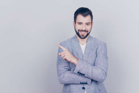 Portrait of young successful brunete  bearded stock-market broker guy on the pure light background, he is smiling, wearing suit and is pointing on a copyspace with his finger