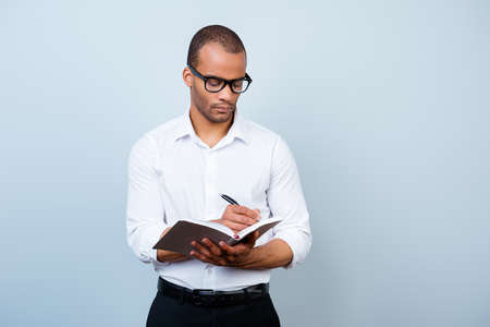 Onderwijs, werk en succesconcept. Nerdy academische Afrikaanse professor is attent, in glazen, met een notebook en schrijft informatie Stockfoto