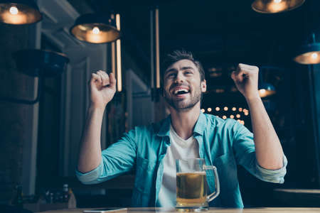 he: Goal! Cheerful young man is happy because of the goal of his favourite team. He is watching game at the fancy cafe with a glass of beer.