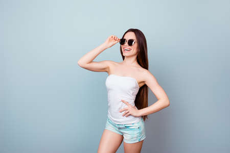Sunglasses and tourism concept. Young cute brunette lady in summer outfit and trendy sun glasses is standing on a light blue background, fixing her eyewear. She is so stylish and attractive Stock Photo