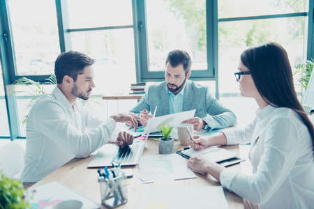 Colleagues are concentrated on serious topic, disscussing the solutions of their company`s problems and sharing opinions and ideas in light modern workplace wearing smart clothes Stock Photo - 87234324