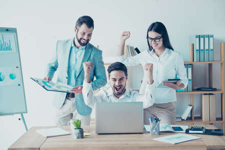 Team of three business partners with raised up hands with fists in light modern work station, celebrating the growth of their company