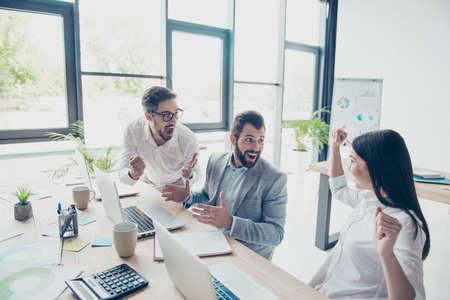 Tres socios comerciales se sorprenden por las buenas noticias, sentados en los lugares de trabajo uno al lado del otro en fila, vestidos con el código de vestimenta de la oficina Foto de archivo - 87234346