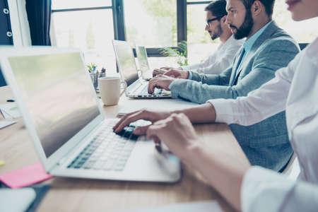 Schließen Sie herauf geerntete Seitenprofilansicht von drei Arbeitern, die in Folge beschäftigt sitzen und auf ihren Laptops schreiben, die entsprechend der Kleiderordnung des Büros gekleidet werden, fokussiert und auf Erfolg konzentriert