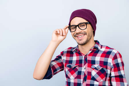 Dreamy student hipster in a casual checkered shirt, black glasses, hat, smiling and looking at the camera, standing on  alight background