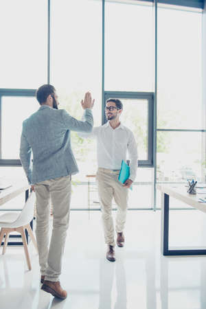 Full size of two handsome brunet guys colleagues, dressed classy and elegant, are giving high five while passing each other in office, successful friendly men Stock Photo