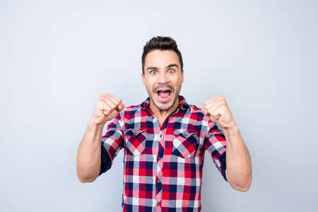 젊은 hipster 스포츠 게임을보고 하 고 순수한 배경에 바둑판 무늬 셔츠에 그의 좋아하는 팀의 승리를 몸짓으로입니다