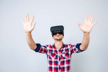 Excited young man is getting experience using VR-headset glasses of virtual reality gesticulating with his hands, in casual chekered wear, isolated on light background