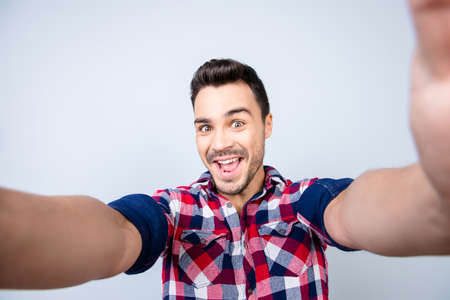 Funky mood of an excited geek young man making selfie shot on camera, standing on a pure background.