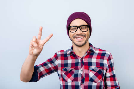 Smiling young nerdy stylish student hipster is gesturing vsign on pure background in black trendy glasses and hat, casual bright checkered shirt