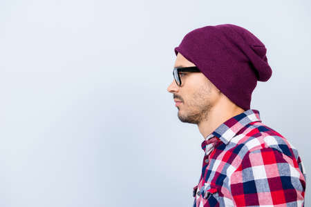 Profile side photo of young serious hipster guy in hat, glasses, with stubble, in casual outfit on pure blue background near the copy space, harsh and brutal