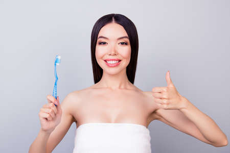 Dental health concept. Gorgeous asian girl in white towel is smiling, on light background, she has a beaming smile Stock Photo