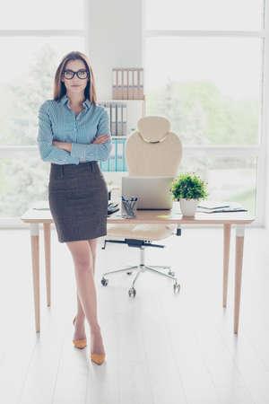 成功の概念。完全な長さの深刻な若いビジネス女性の経済学者メガネと厳格なフォーマルウェアは、彼女のオフィスに立って