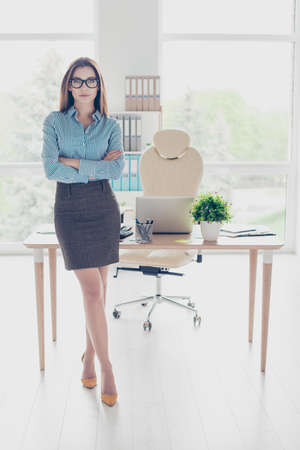 Success concept. Full length portrait of serious young business lady economist in glasses and strict formal wear, standing at her office