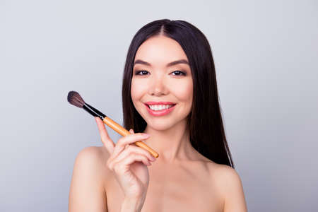 Sensual pretty asian young woman is holding make up brush for powder, smiling, standing on pure background Stock Photo