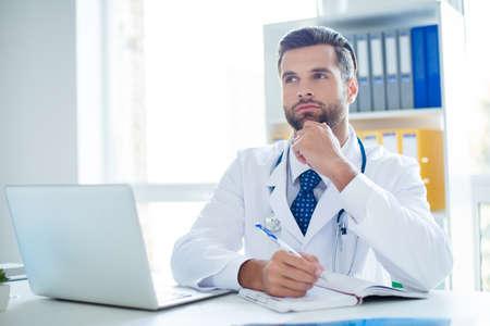 白い制服とネクタイで医学の若いハンサム髭の教授は、患者の苦情を聞いている間、彼の近代的な職場で医療業界の革新を考えています