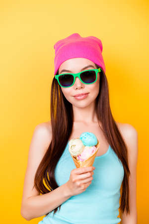 Asian funky hipster is posing for photo, wearing tourist`s outfit, glasses, hat, holds ice cream, so cool, attractive and  imposing!