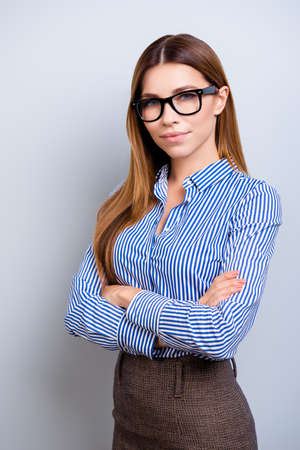 Young successful and confident  business lady is standing with crossed hands and looks in camera. She is wearing smart formal clothes and glasses, behind her is a pure background