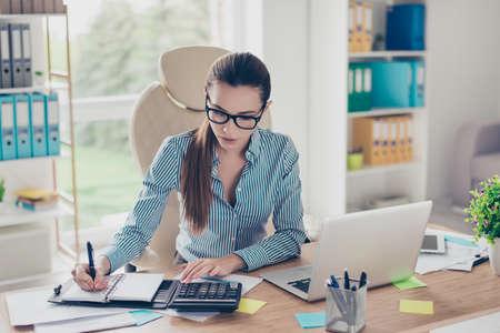 Retrato del contable de la empresaria joven seria en ropa formal y con el cuento del potro, sentándose en su lugar de trabajo y haciendo notas