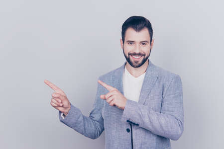 Young handsome brunet bearded businessman lawyer in grey jacket stands on pure light background, shows at the copy space near him. Advertising concept Stock Photo
