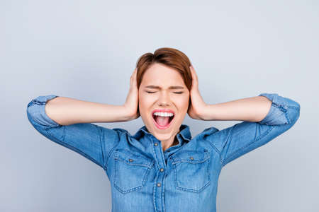 Irritated young woman in jeans shirt doesn't want to hear noise and covers her ears with hands Stock fotó - 86412540