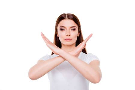 Jeune femme brune fait un geste d'arrêt, debout en tenue blanche, sur un fond blanc, sérieux Banque d'images - 86412542