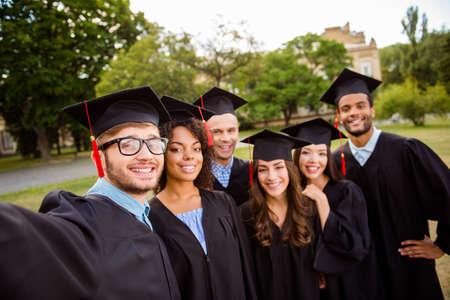 6人の留学生が、学校の外で、オタクの男が取っている selfie 撮影のためにポーズをとっています。モルタルボードで、陽気な、スマートで成功した若者の収集、ガウン 写真素材 - 87234514