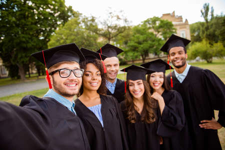 Six international students are posing for selfie shot, that nerdy guy is taking, outside school building. Gathered, cheerful, smart and successful youth in mortar boards, gowns