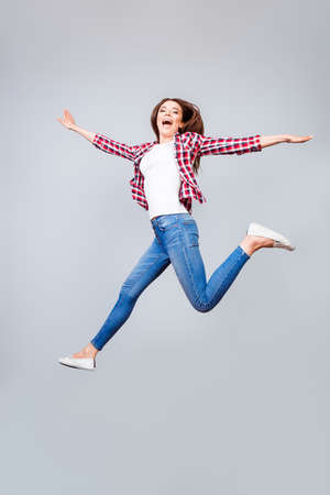 Very excited happy cute brunette girl is jumping up, wearing casual clothes, white shoes, on pure light blue background, amazed