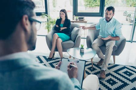 黒髪髭夫が彼の妻、彼女のせいで指している怒っている若い心理学者は、フォーマルな服装を着てに座る。 写真素材