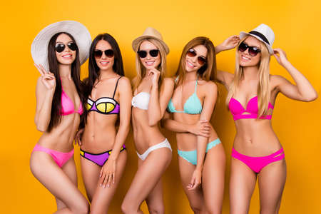 Five hot chicks are posing in trendy swimming suits and sunglasses, caps. They are protecting their healthy nice hair, skin and eyes from the strong sun. Summer, joy, hen party, playful mood