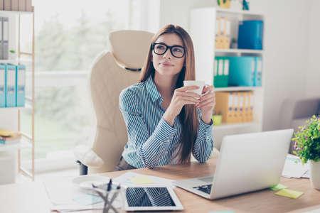 Exitoso abogado soñadora dama de negocios relajada está descansando en su lugar de trabajo y toma café, mirando a otro lado encantado Foto de archivo - 87067712