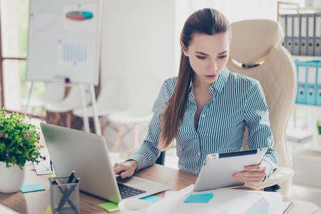 Retrato del contable serio joven de la empresaria en ropa formal y con el cuento de potro, sentándose en su lugar de trabajo y concentrado en datos en la computadora portátil y la tableta