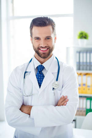 Authority and success concept. Young handsome and stylish professor of medicine in white uniform is standing at his work place with crossed hands, smiling