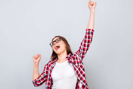 Very excited happy girl is jumping up, wearing casual clothes, on pure light blue background