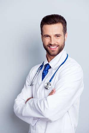 権威と成功のコンセプトです。白い制服の医学部の若いハンサムでスタイリッシュなひげを生やした教授は笑顔と純粋な白の背景に立っています。